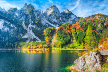 autumn scenery with Dachstein mountain summit reflecting in crystal clear Gosausee mountain lake