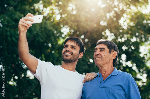 Fotografie, Obraz  Selfie portrait of father and adult son outdoor