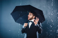 Cheerful Handsome Bearded Young Businessman Posing With Umbrella Under The Rain And Showing OK Sign, On Blue Background