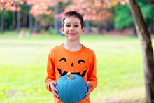 Joyful Boy With A Teal Pumpkin...