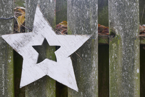 Fotografering  folk art star on a rustic wooden fence