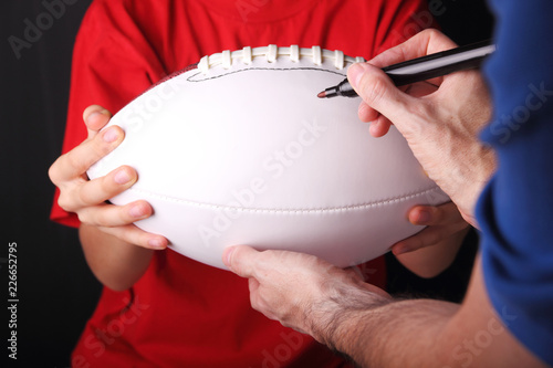 Photo Young football fan getting an autograph on a new white blank football