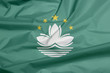 Fabric flag of Macau. Crease of Macau flag background, green with a lotus and stylised Governor Nobre de Carvalho Bridge and water in white, and five gold star.