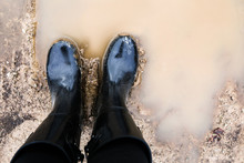 Black Boots Standing In Muddy Water