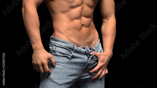 Closeup torso of shirtless muscular man posing on a black background Canvas Print