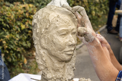sculptor creates a bust and puts his hands clay on the skeleton of the sculpture. Close-up