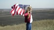 A young beautiful girl is holding a USA flag, which is developing in the wind.