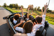 Young girls and guys are sitting in a black cabriolet, holding their hands up and making selfie on a warm sunny day.