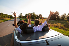 Black Cabriolet Is On The Country Road. Company Of Young Girls And Guys Are Sitting In The Car Hold Their Hands Up On A Sunny Day.