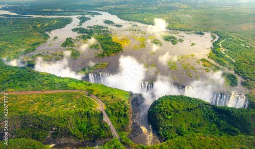 Fototapeta premium Wodospady Wiktorii w Zimbabwe i Zambii, zdjęcie z helikoptera z lotu ptaka, zielony las wokół niesamowitych majestatycznych wodospadów Afryki. Livingston Bridge nad rzeką