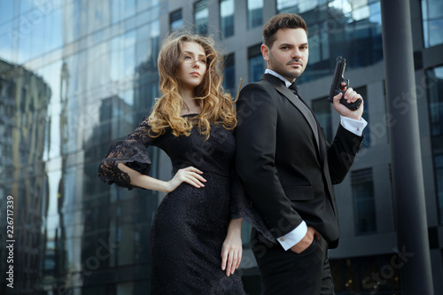 Photo  An elegant man with pistols in his hands protects a beautiful girl