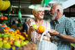 canvas print picture Smiling senior couple holding basket with vegetables at the market