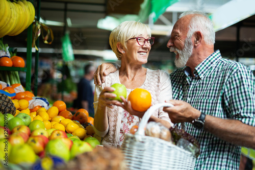 Photo  Smiling senior couple holding basket with vegetables at the market