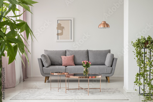 Stampa su Tela Real photo of a comfy sofa, copper coffee table and plants in a bright living ro