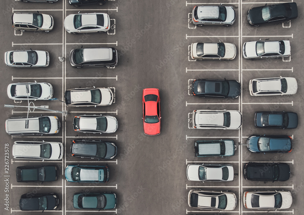 Fototapeta Top view of the crowded Parking lot with quadcopter or drone. Original bright automobile among the grey of mediocre cars. Parking space search, No parking space