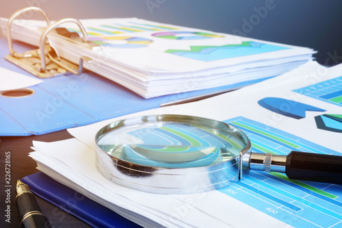 Financial audit report and magnifying glass on a desk. Wallpaper Mural