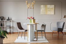 Real Photo Of An Elegant Dining Room Interior With Golden Accents, Table, Chairs And Painting On A Wall