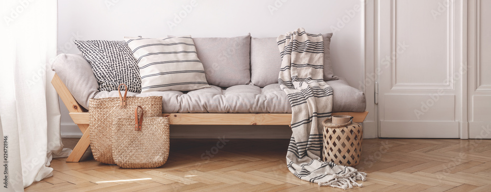 Fototapety, obrazy: Panorama of pillows and blanket on wooden beige couch in white flat interior with door. Real photo