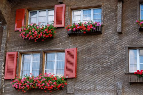 Foto op Plexiglas Historisch geb. Typical Switzerland wooden house windows decorated by flower