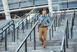 Fototapeta Na drzwi - smiling middle aged businessman holding paper cup and smartphone while walking down on stairs