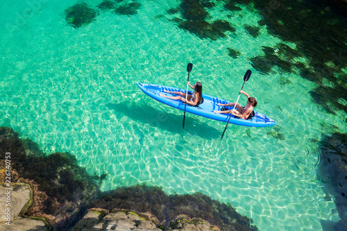 Two young women kayaking in the sea. Beautiful woman canoeing on the island on a summer day.