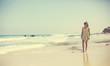 12 years old girl teen girl in yellow dress walking on seaside. Summer vacation