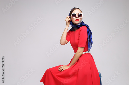 Young woman in retro style. Sunglasses and silk scarf. Fototapete