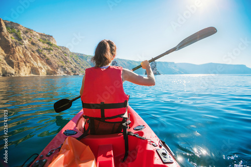 Kayaking. A Woman in a Kayak. Girl Paddling in the Calm Sea water near the rocky coast.