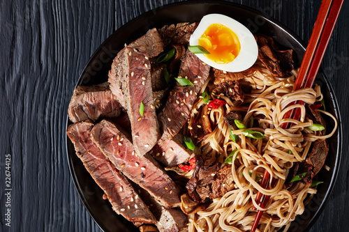 Photo  black bowl of Soba noodles with sliced roast beef