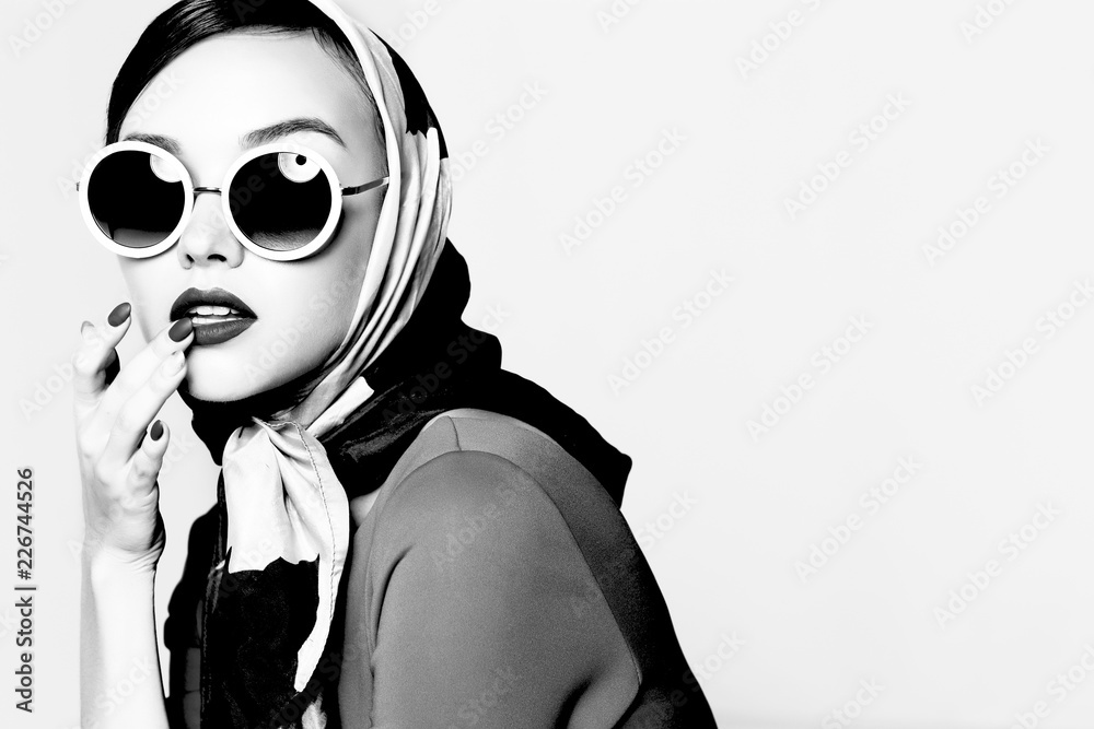 Fototapeta Young woman in retro style. Sunglasses and silk scarf.