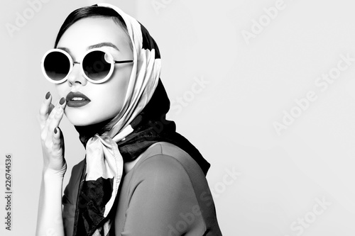 Photographie  Young woman in retro style. Sunglasses and silk scarf.