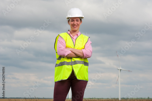 Portrait of a successful young woman the chief architect in a green waistcoat and a helmet against the background of windmills and a blue sky Fototapeta