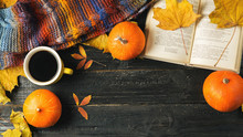 A Mug Of Hot Coffee, A Warm Scarf And A Book On A Dark Wooden Table Strewn With Autumn Leaves