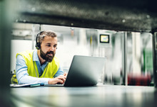 An Industrial Man Engineer With Headset And Laptop In A Factory, Working.