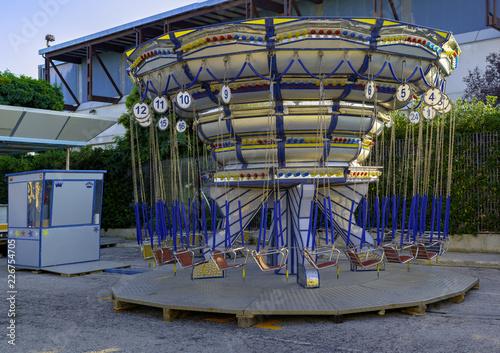 Zdjęcie XXL Empty Carousel Merry-Go-Round z miejscami zawieszonymi na łańcuchach bez ludzi czekających na swoich gości. Letni wieczór w miejskim parku rozrywki.