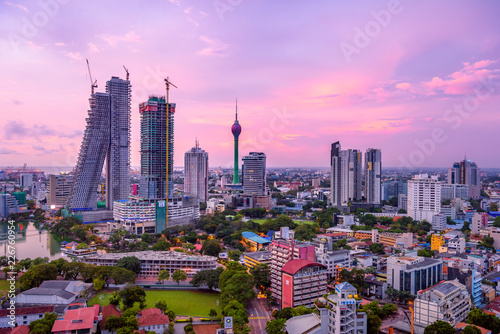 Photo Stands New York Colombo Sri Lanka skyline cityscape photo. Sunset in Colombo with views over the biggest city in Sri Lanka island. Urban views of buildings and the Laccadive Sea