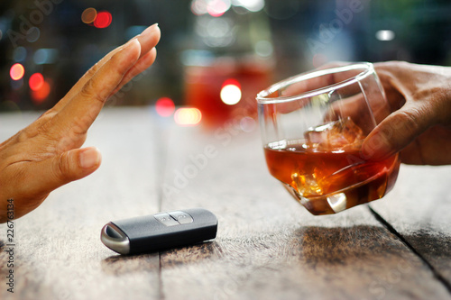 Foto auf Leinwand Alkohol Male hands with car key on table rejecting alcoholic glass beverage on colorful background