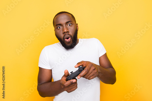 Photo  Portrait of shocked funny funky crazy mulato man, playing online