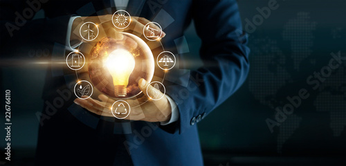 Businessman' s hand holding glowing light bulb with energy sources icon Wallpaper Mural