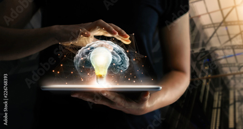 Human holding tablet with light bulb future technology, brain and network connection on communication background, science, innovation and creative idea concept.