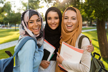 Arabian Women Students Holding Books In Park Outdoors.