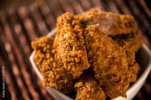 Fototapeta Bucket full of crispy kentucky fried chicken with smoke on brown background. Selective focus. obraz