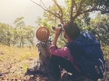 The Tourist Couple Sitting Use Binoculars On The Mountain.