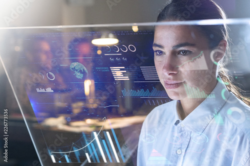 Portrait of a beautiful woman (girl) while she is looking at a futuristic screen with holograms and the office in the background. Concept: Future, Technology, work