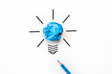 Inspiration And Great Idea Concept. Light Bulb With Crumpled Colorful Paper And Blue Pencil On White Background.