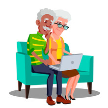 Multi Ethnic Couple Sitting On The Couch With Cup And Laptop Vector. Isolated Illustration