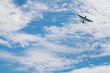 canvas print picture - Plane biplane flies in the sky. Bottom view of the plane. Silhouette of the aircraft against the blue sky. Flying light aircraft blue on a background of white clouds.