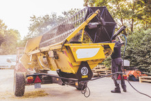 The Mechanics Repair The Yellow Combine Harvester In The Farm Yard.