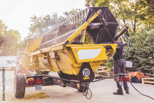 Fotografía The mechanics repair the yellow combine harvester in the farm yard