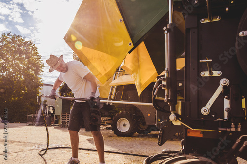 Fotomural  The mechanics repair the yellow combine harvester in the farm yard